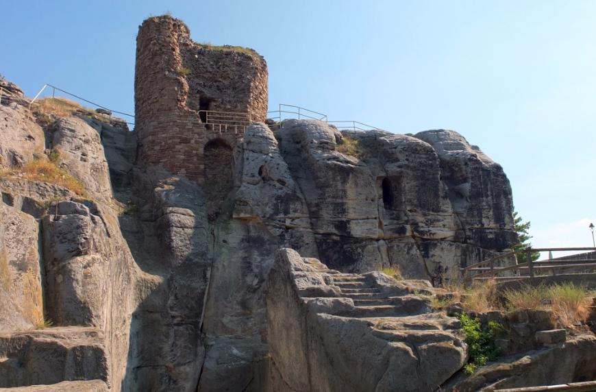 Reste des Bergfrieds der Felsenburg, davor der Halsgraben, über den eine Toranlage führte.